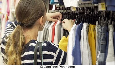 Young mother shopping for childrens clothes in a retail clothing store. Viewing items.