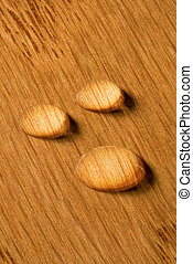 Three water droplets on wooden plank - Three round water...