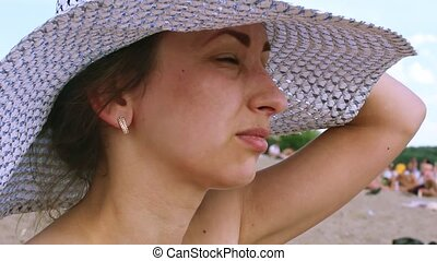 Young woman with hat sunbathing on the beach