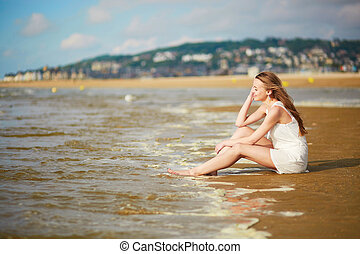 Beautiful young woman enjoying her vacation by ocean or sea