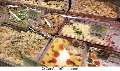 Many prepared salads and cheese in the refrigerator in a...