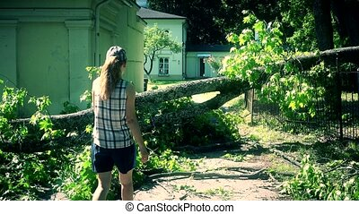 Worried woman climbing over fallen tree on house yard...