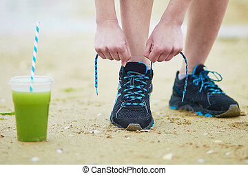 Young jogger with green vegetable smoothie, tying sport...