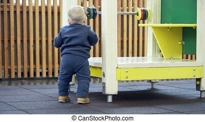 A little boy trying to climb in house on the playground....
