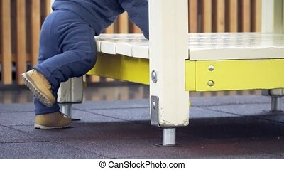 A little boy trying to climb in house on the playground. Legs close-up.