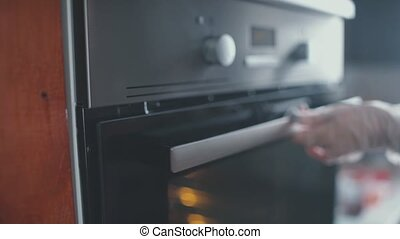 Unknown woman in her kitchen puts her cake into the oven. -...