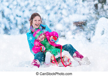 Mother and child sledding in a snowy park - Young mother and...