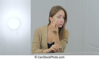 Beautiful young woman applies concealer foundation cream...