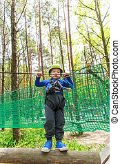 Young boy in helmet walks by rope at sunny summer day in...