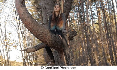 A girl with long loose bright brown, almost ginger, hair and a few locks in the front dyed yellow, green and blueclimbing down from the tree.wags her head from one side to the other.