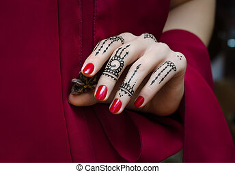 Woman Hands with black mehndi tattoo and ren manicure