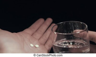 Pills and glass of water in hand isolated black background Man taking pills POV