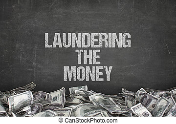 Laundering the money text on black background with dollar...