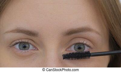 Beautiful young woman putting mascara - Close up shot....