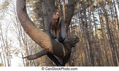 While on the tree, a girl smiles and wags her head in...