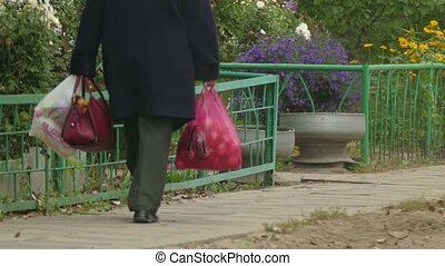 old woman carries shopping bags in the shop coat autumn outdoor