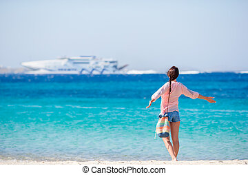 Young girl on the beach background big cruise liner. Woman...