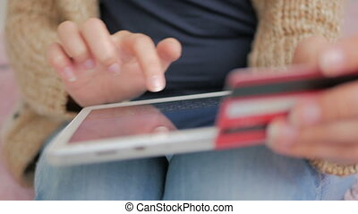 Woman shopping online at digital tablet with credit card -...