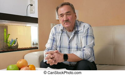Senior man mustache thoughtfully looking at the camera. He sits on the couch at home and thinking about life.