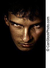 Scary face in the shadow - Low key portrait of evil looking...