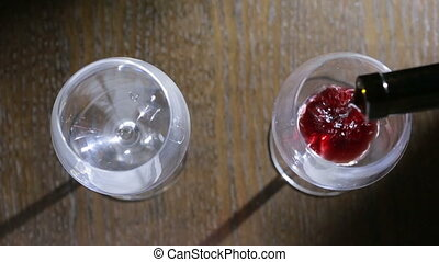 to pour two glasses of red wine. top view. Male and female hands