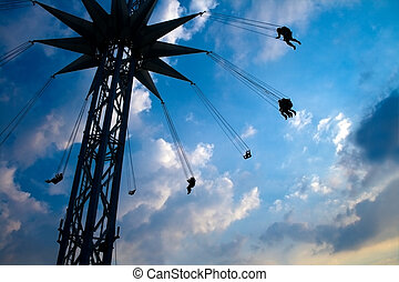 Flying people on swinging carousel - Silhouette of flying...