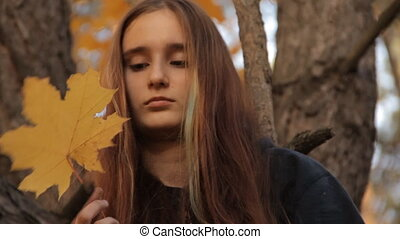 A girl with long loose hair. Twisting a maple leaf in her hands thoughtfully and rubbing it along the fibers and edges.