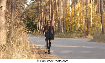 A girl with long loose hair walking along the roadside with...