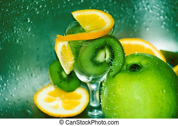 Fruits and water - Slices of oranges and kiwi and an apple,...