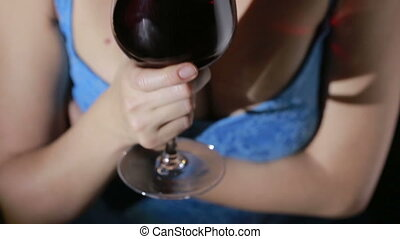 woman with big breasts holding a glass of red wine. close-up