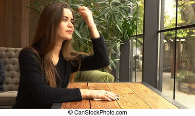 Young woman at cafe using mobile phone - Young woman at cafe...