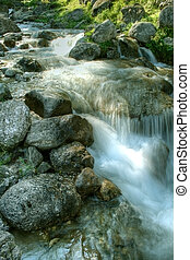 Water falling through mountain rocks - Picturesque scenery -...