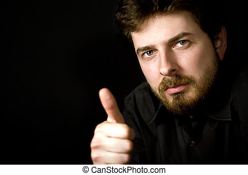 Confident man showing thumb up, on black background