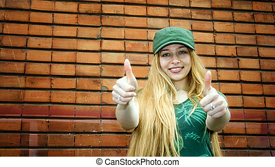 Smiling blonde showing thumbs up - Cute smiling blond girl...