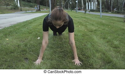 An athletic girl doing a Plank exercise on a green lawn with her hands rested on the ground.