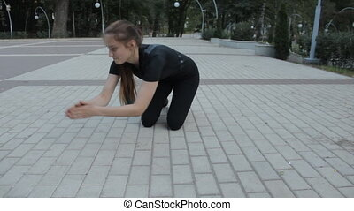 A fitness fan dressed in black apparel. doing pushups in a...