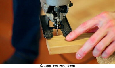 man adjusts electric jigsaw - the young man adjusts electric...