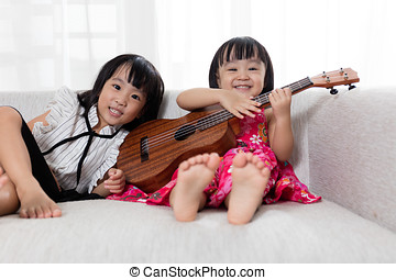 Asian Chinese little sister playing ukele - Asian Chinese...
