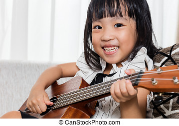 Happy Asian Chinese little girl playing ukele - Happy Asian...