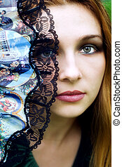 Beautiful woman hiding behind fan - Portrait of beautiful...