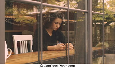 Young woman at cafe using mobile phone