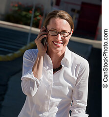 Beautiful woman smiles as she talks on cell phone.