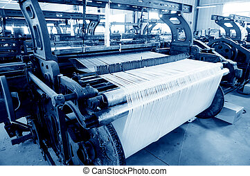 Old weaving machine - A row of textile looms weaving cotton...