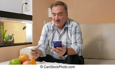 Senior man with a mustache makes a purchase from the online...