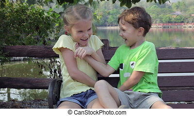 Happy children sitting on bench near a pond at the day time.