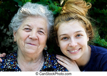 Young woman hugging her grandmother - Portrait of young...