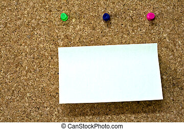 Blank reminder on wooden board and three colorful pins