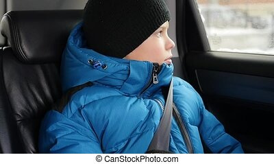 the child rides in the car in the backseat and looking out...