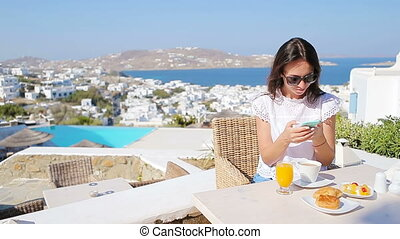 Beautiful elegant lady on breakfast with phone at outdoor cafe with amazing view on Mykonos town.