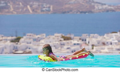 Adorable girl with inflatable air mattress in outdoor swimming pool background Mykonos town